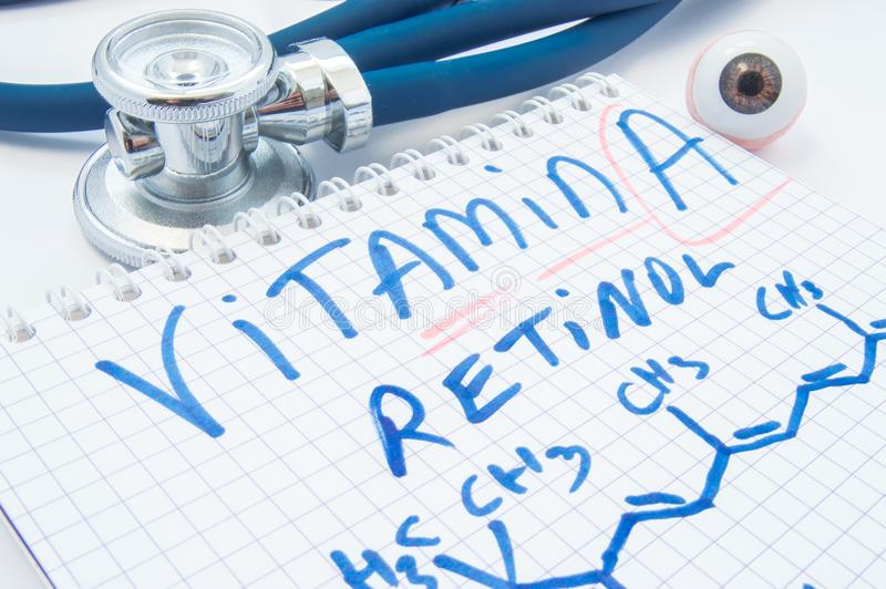 Note with inscription Vitamin A Retinol and chemical formula is close to figure of human eye and stethoscope. Value of vitamin A royalty free stock photos