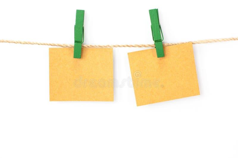 Note la tarjeta, el papel marrón y los clips de madera imagen de archivo libre de regalías