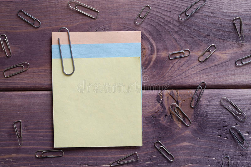 Note, memo, memorandum. Yellow sticky note with paper clips are on a wooden table stock image