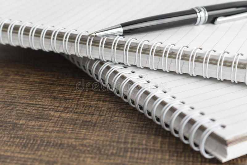 Note pad and pen on the wooden table royalty free stock photography