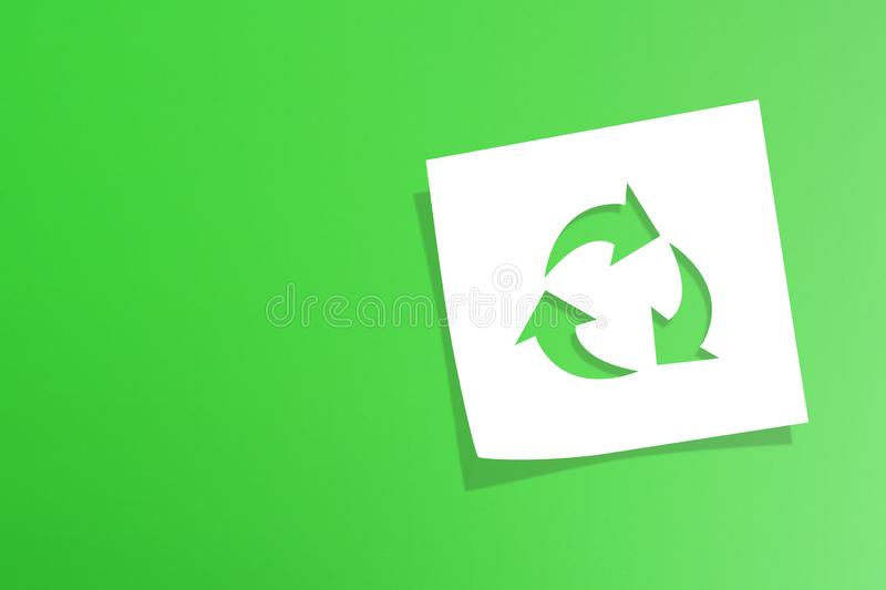 Note paper with recycle symbol on green background. Note paper with recycling symbol on green background stock photo