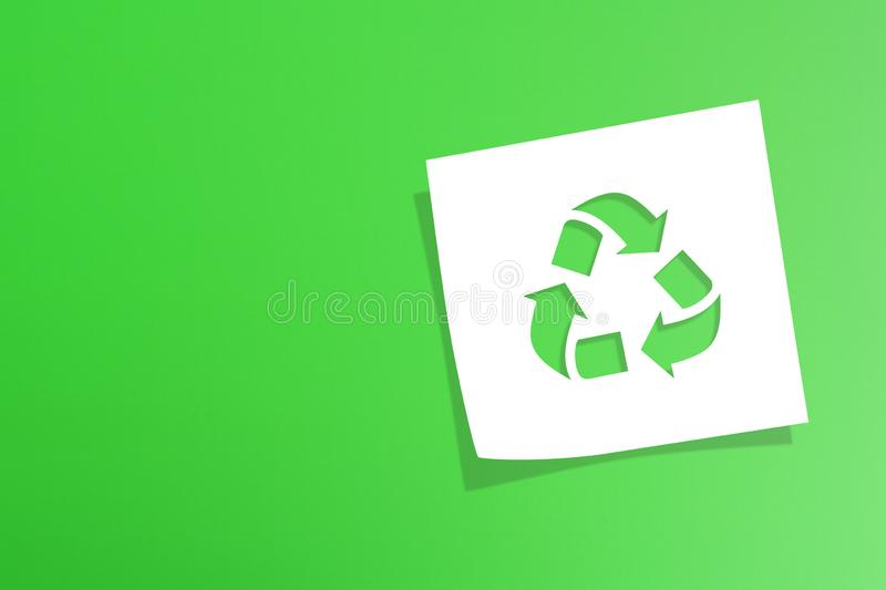 Note paper with recycle symbol on green background. Note paper with recycling symbol on green background stock image