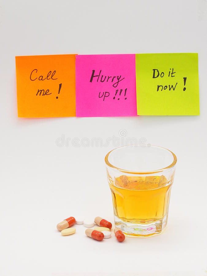 Note papers, alcohol and pills. Colorful note papers with stressful work instructions, a glass of hard alcohol and a pile of pills around it stock image