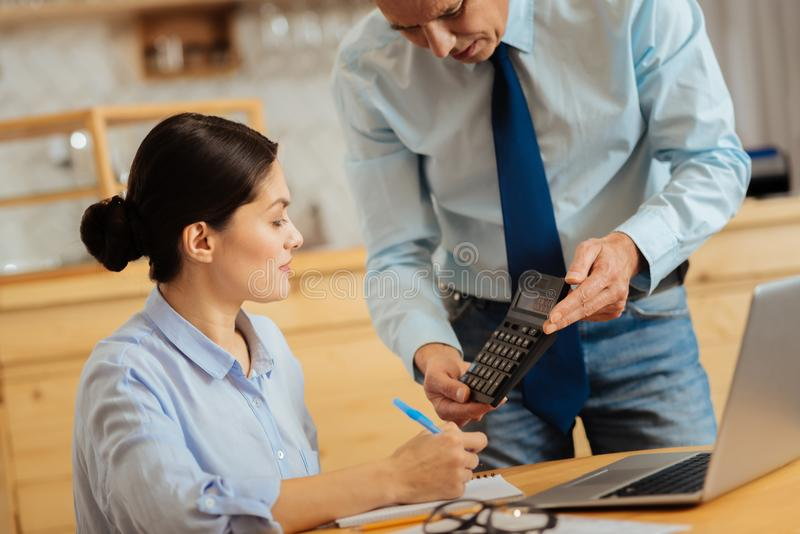 Pretty diligent employee sitting and looking at the calculator. Note it. Pretty diligent confident employee sitting in the room by the table near her boss royalty free stock photography