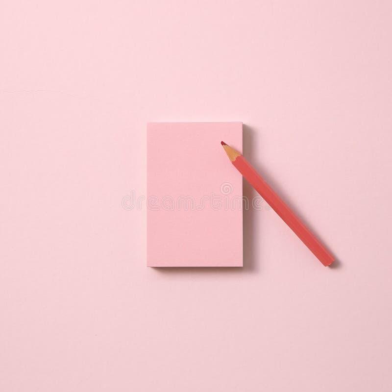 Note rose de note et crayon coloré rose sur le fond rose images stock