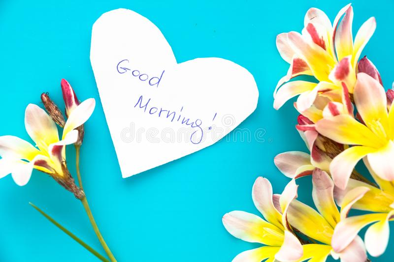 Note in shape of heart with words Good Morning. Note in shape of heart with words Good Morning, with flowers on blue surface royalty free stock photography