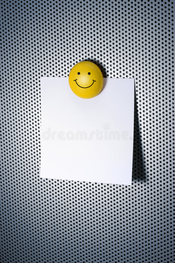 Note with Smiley Magnet. A note on a modern bulletin board with a smiley magnet stock photos
