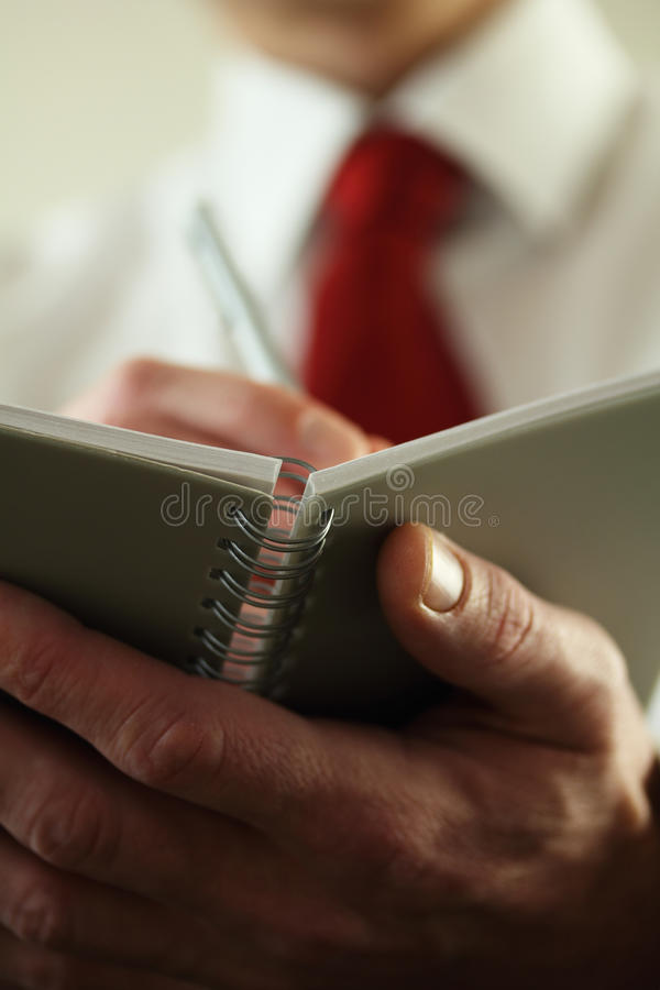 Note Taking. Business man or Office worker taking important notes royalty free stock images