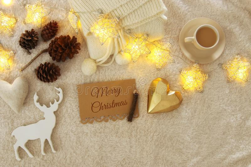 note with text MERRY CHRISTMAS and cup of cappuccino over cozy and warm fur carpet. Top view. royalty free stock photos