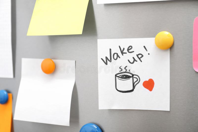 Note with text `Wake up` and empty sheets on refrigerator door. Space for text royalty free stock image