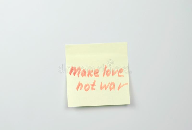 Note on yellow sticker paper sheets with motivation words make love not war. stock images