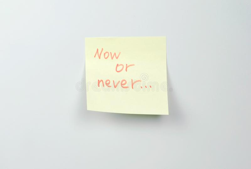 Note on yellow sticker paper sheets with motivation words now or never. Note on yellow sticker paper sheets with motivation words now or never royalty free stock photos