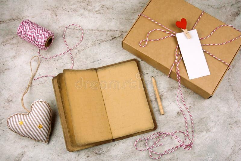 noteboock ouvert avec le vieux papier de cru, crayon, boîte-cadeau avec le label blanc vide, coeurs photo stock