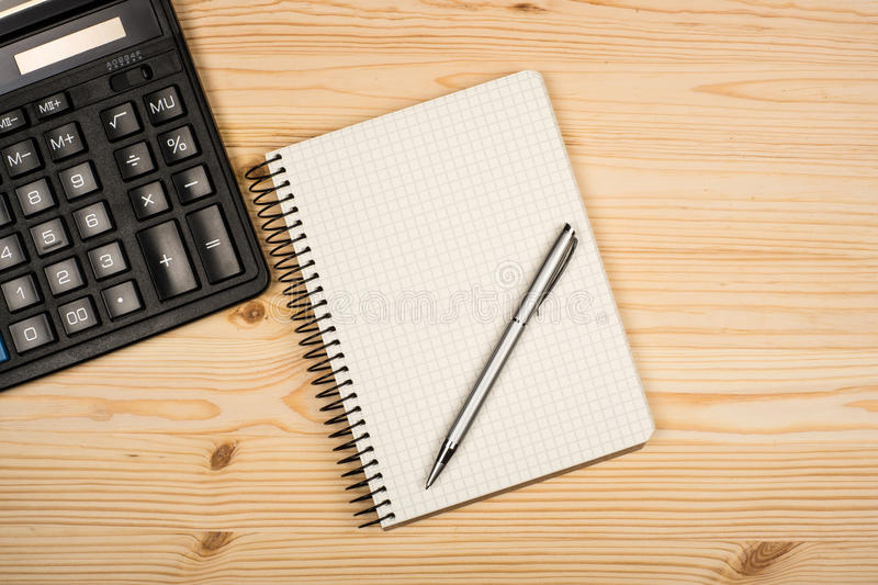 Notebook, ballpen and calculator. On wooden desk royalty free stock photography