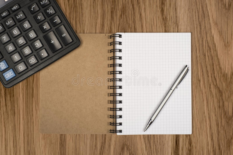 Notebook, ballpen and calculator. On wooden desk royalty free stock images