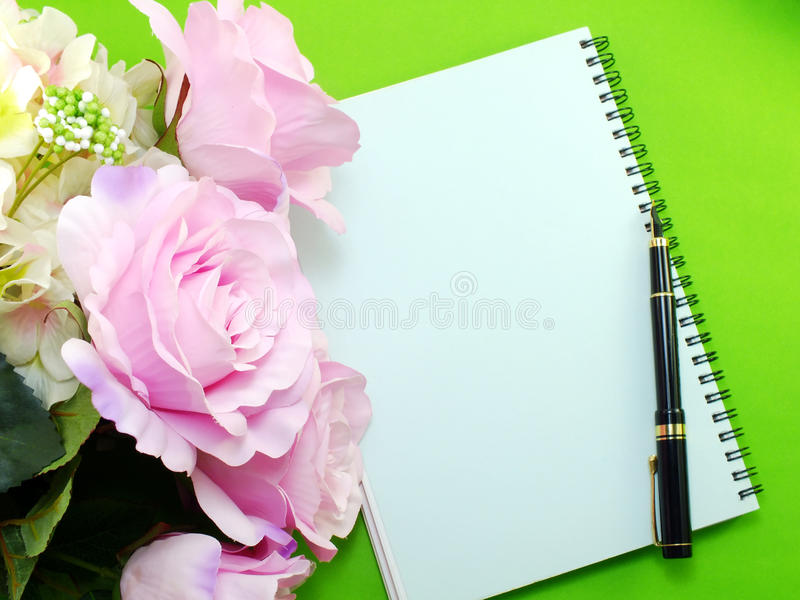 Notebook and beautiful pink roses artificial flowers bouquet. Open notebook and beautiful pink roses artificial flowers bouquet royalty free stock photo