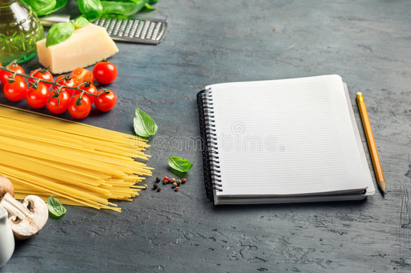 Notebook with blank pages and ingredients for cooking Italian pa. Sta on dark stone surface stock image
