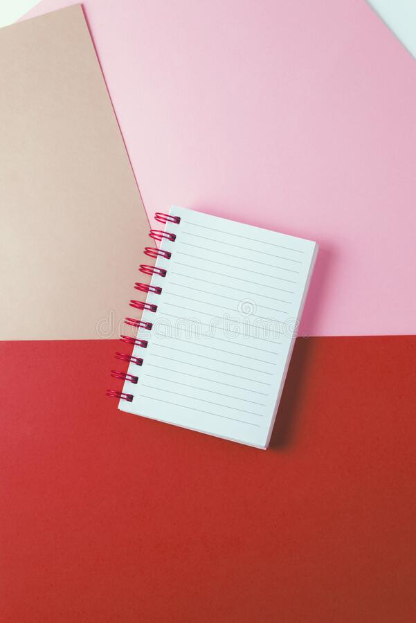 Notebook with blank sheet and golden spiral on a colorful pastel background stock photos