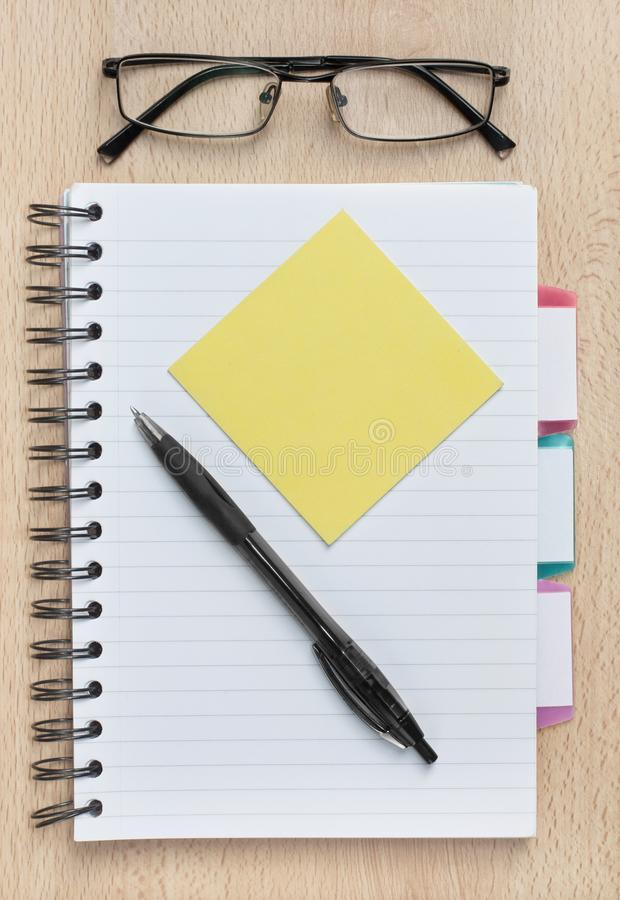 Notebook with blank sticky note on an office or home desk, with copy space. Notebook with blank sticky note on an office or home desk, with glasses and pen and royalty free stock image