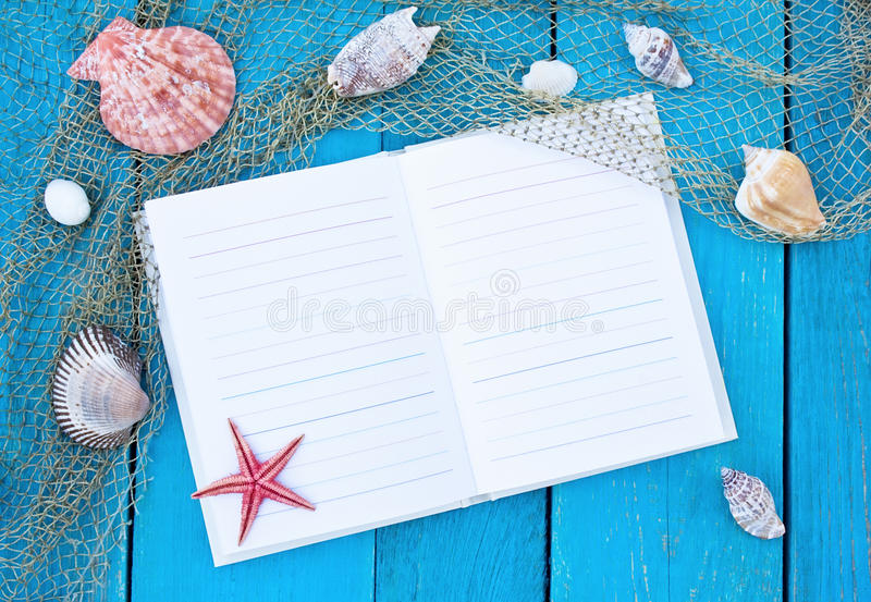 Notebook on blue table with cockleshells and red starfish stock photos