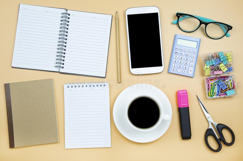 Notebook brown cover mobile phone calculator and black coffee white cup green glasses on orange background pastel style with copy stock photo