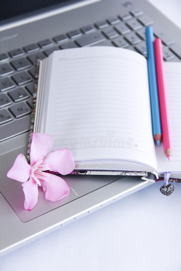 Notebook for business, pink and blue pencils and laptop computer keys. Notebook for business, pink and blue pencils and laptop computer a keys stock photos