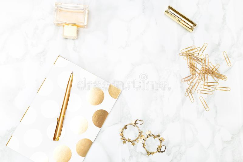 Notebook c of office items of gold color and cosmetics on the de. Sktop. Top view royalty free stock image