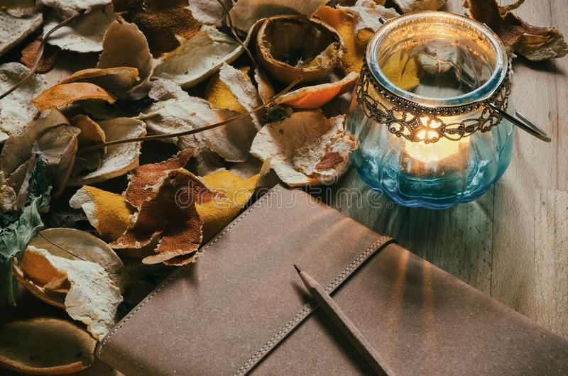 Notebook and a candle lantern with dried citrus peel royalty free stock photo