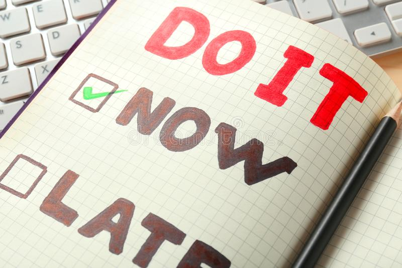 Notebook with choice DO IT NOW or LATER and keyboard, closeup stock image