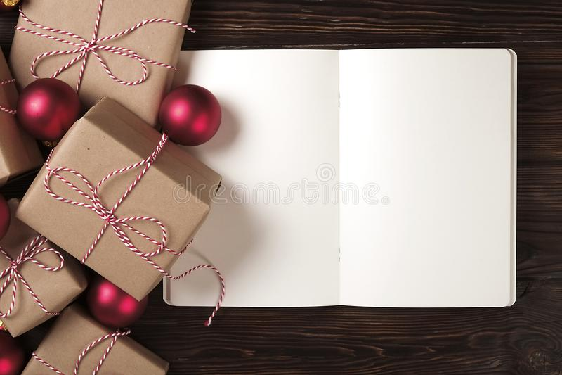 Notebook with christmas decoration and gifts on wooden background. To do list, santa letter concept. Top view, flat lay, text spac. Female hands writing royalty free stock image