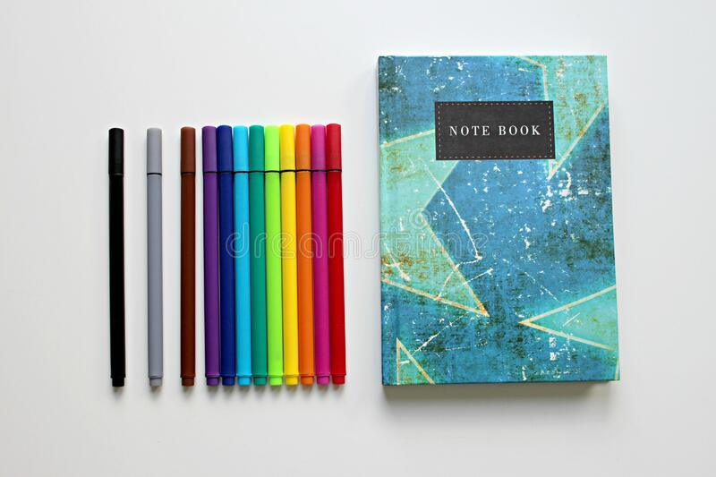 Notebook and colored pens royalty free stock image