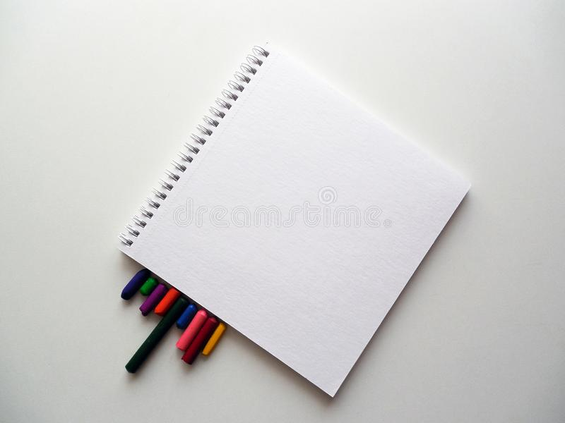 Notebook and coloured crayons in white stock photo