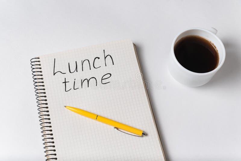 Notebook com inscrição LUNCH TIME Taça de café e fundo branco de caneta foto de stock