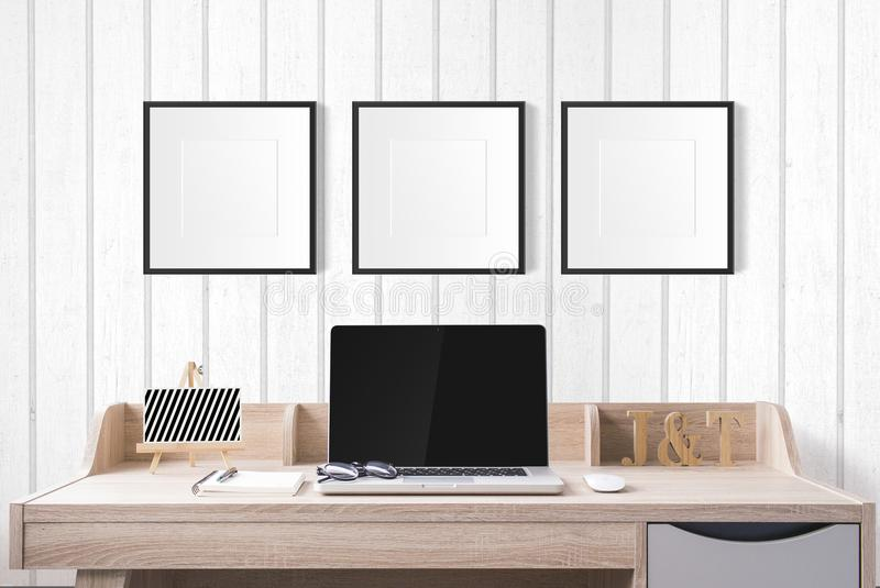 notebook computer and stationery on working table with blank photo frames in the studio with white wood wall. royalty free stock photos