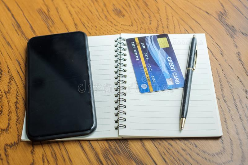 Notebook, credit card and touchscreen smartphone on table. business, lifestyle, technology, ecommerce and online payment concept.  stock photography