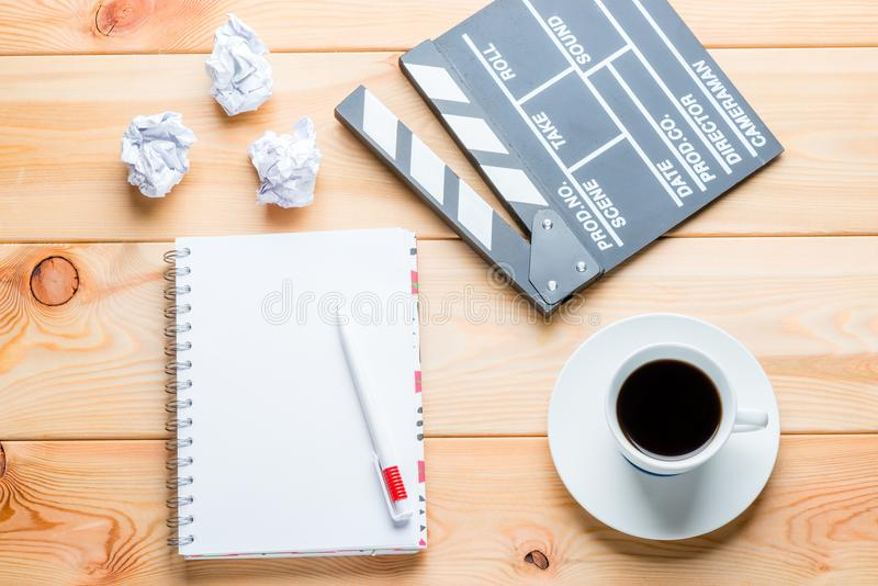 A notebook, a cup of coffee and a clapper for shooting movie episodes on wooden boards royalty free stock photo