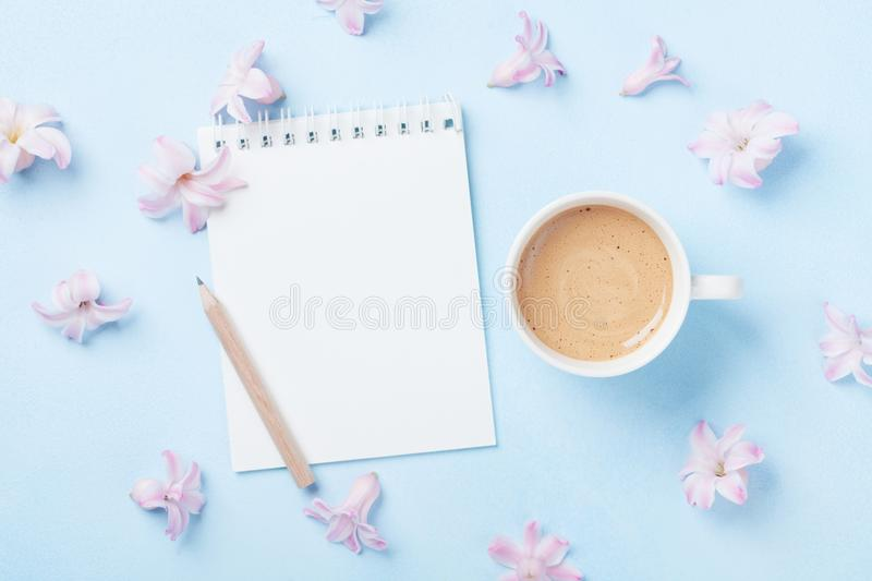 Notebook, cup of coffee and pink flowers on blue pastel background top view. Fashion woman working desk. Spring do list. Flat lay. Notebook, cup of coffee and stock images