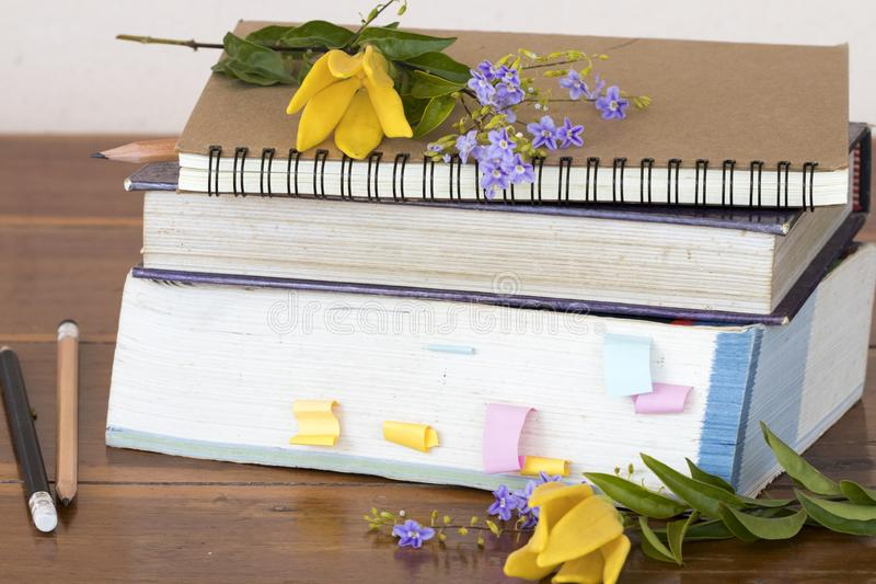 Notebook ,dictionary book and pencil of student for study. With flower ylang ,purple flower  decoration on table royalty free stock photos
