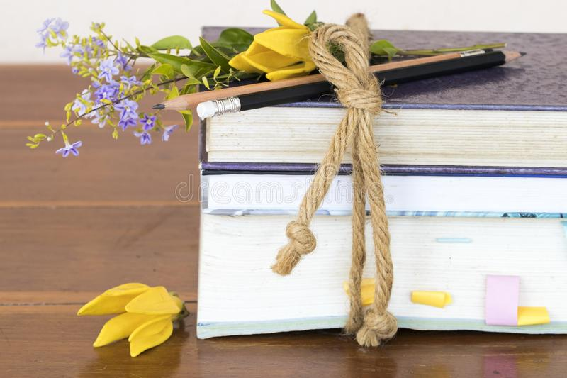 Notebook ,dictionary book and pencil of student for study. With flower ylang ,purple flower  decoration on table stock image