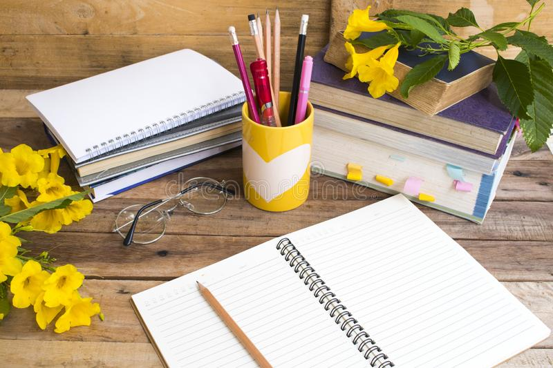Notebook ,dictionary english and all book for study. Of student  with stationary ,yellow flowers decoration on background wooden royalty free stock images