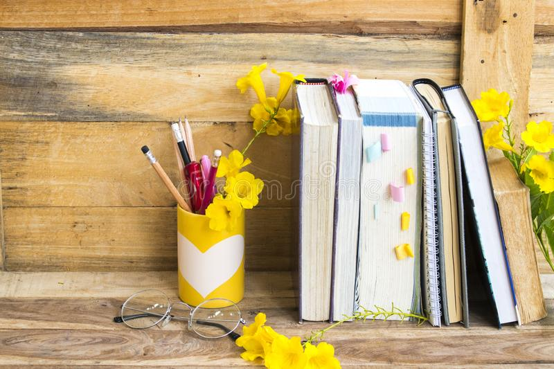 Notebook ,dictionary english and all book for study. Of student  with stationary ,yellow flowers decoration on background wooden royalty free stock photos