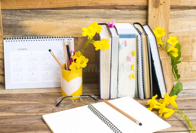 Notebook ,dictionary english and all book for study. Of student  with stationary ,yellow flowers decoration on background wooden stock photo