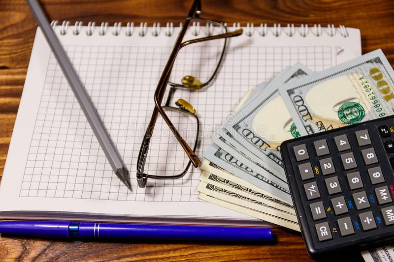 Notebook with dollars, pen, glasses and calculator on wooden desk. Financial concept. Business accounting royalty free stock photography