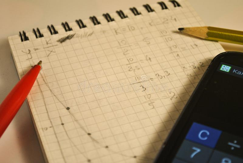 Notebook, formulas, mathematical graphics, homework, mobile phone stock photography