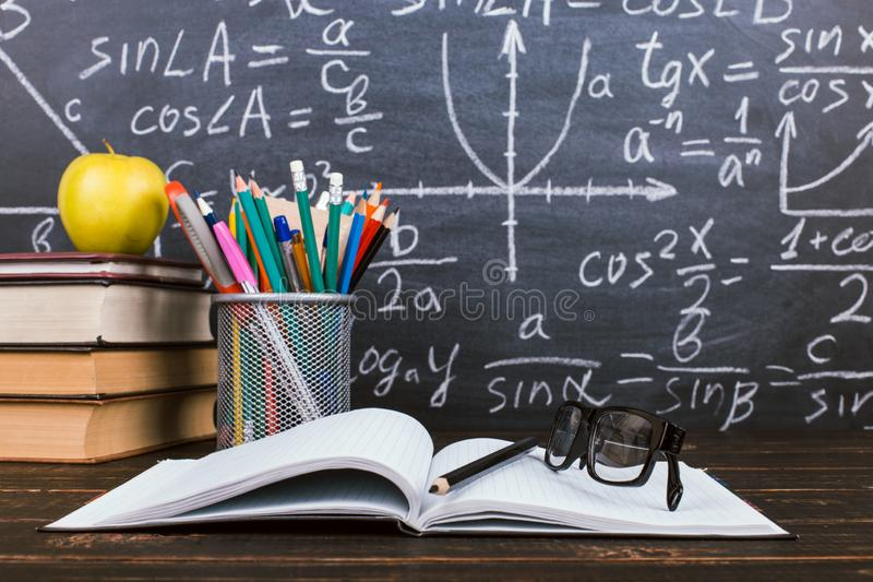 Notebook, glasses, apple and a glass with pencils on chalkboard background with formulas. Teacher`s day concept and back to schoo. Notebook, glasses, apple and stock photography