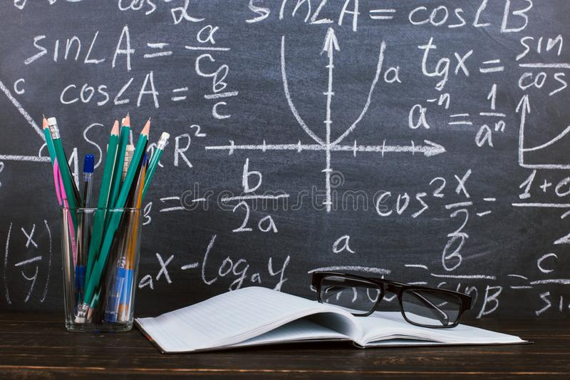 Notebook, glasses and a glass with pencils on chalkboard background with formulas. Teacher's day concept and back to school stock photos
