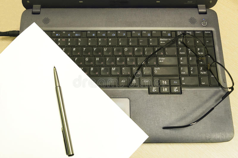 Notebook, glasses and paper with pen on keyboard background. royalty free stock photos