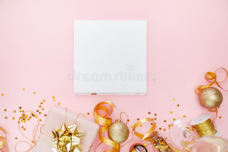 Notebook  with golden bow on pink coral background with stars and sparkles. Festive  and wish list . 2020 New Year concept copyspace top horizontal view royalty free stock image