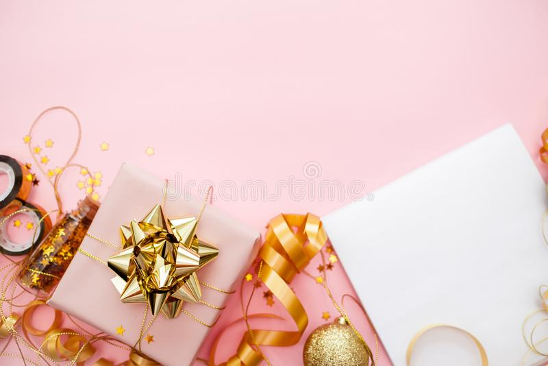 Notebook  with golden bow on pink coral background with stars and sparkles. Festive  and wish list . 2020 New Year concept copyspace top horizontal view royalty free stock photos