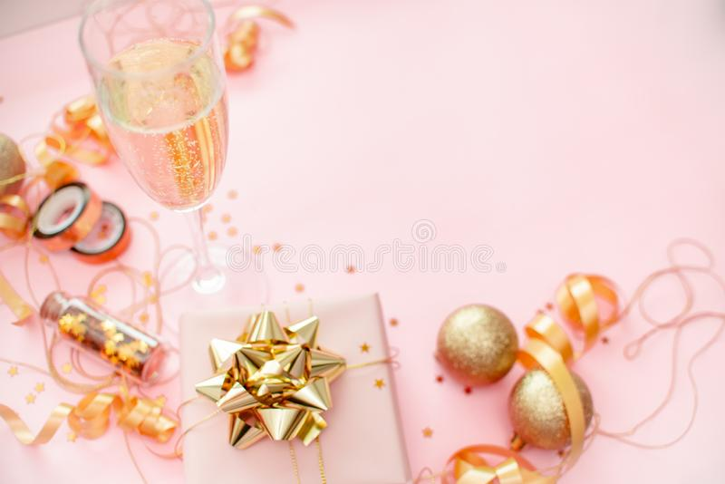 Gift box with golden bow on pink coral background with stars and sparkles. Festive concept copyspace top horizontal view. 2020 New Year concept copyspace top stock photo